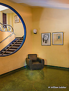 Art Deco sitting area with terrazzo floors and staircase to balcony.