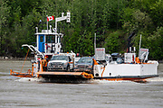 In Yukon, Canada, the free George Black Ferry connects Dawson City to West Dawson and the Top of the World Highway, which goes to the Yukon-Alaska border. It is a drive-on/drive-off single deck ferry, operating 24 hours per day in summer. The remote 65-mile Top of the World Highway connects the Klondike Loop from Dawson City with the Taylor Highway (which links Chicken, Eagle and the Alaska Highway). Dawson City was the center of the Klondike Gold Rush (1896–99), after which population rapidly declined. Dawson City shrank further during World War II after the Alaska Highway bypassed it 300 miles (480 km) to the south using Whitehorse as a hub. In 1953, Whitehorse replaced Dawson City as Yukon Territory's capital. Dawson City's population dropped to 600–900 through the 1960s-1970s, but later increased as high gold prices made modern placer mining operations profitable and tourism was promoted. In Yukon, the Klondike Highway is marked as Yukon Highway 2 to Dawson City.