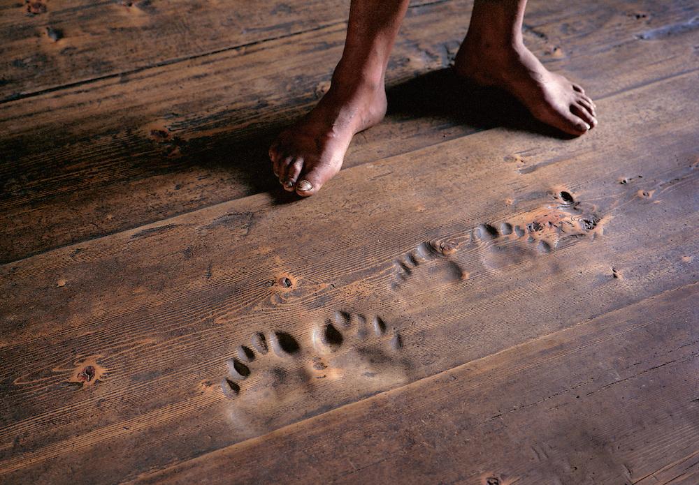 Footprints worn in to wooden floorboards from 50 years of Buddhist prayer prostrations. Chozo village, Lunana Region, the Snowman Trek, Bhutan.