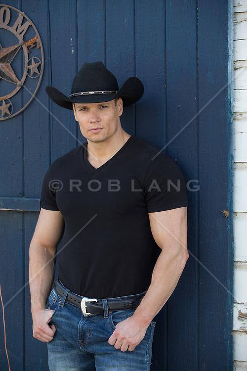handsome cowboy by a horse barn