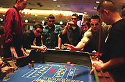 Group playing the tables at a casino, one man wearing Elvis style sunglasses, Las Vegas, USA, 2000's