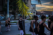 Students of the Manguinhos community ballet walks past abandoned buildings and unattended garbage as they head to the library they are using as their training centre  in Manguinhos neighbourhood in Rio de Janeiro, Brazil, Monday, June 11, 2018. The Manguinhos community ballet has been a reprieve from the violence and poverty that afflicts its namesake neighborhood for hundreds of girls who have benefitted from free dance classes since 2012. (Dado Galdieri for The New York Times)