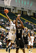 Raider freshman Reggie Arceneaux (3) goes for a layup as Vandal junior Mansa Habeeb (3) goes for a rebound in the first half as the Idaho Vandals play the Wright State University Raiders at the Nutter Center, Tuesday, December 20, 2011.