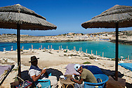 Lampedusa, Italia - luglio 2011. Due venditori ambulati attendono l'arrivo di turisti su una delle spiagge di Lampedusa. A causa della emergenza immigrazione dello scorso inverno, il turismo ha subito un calo del 70%. La crisi influisce anche sul lavoro degli ambulati..Ph. Roberto Salomone Ag. Controluce