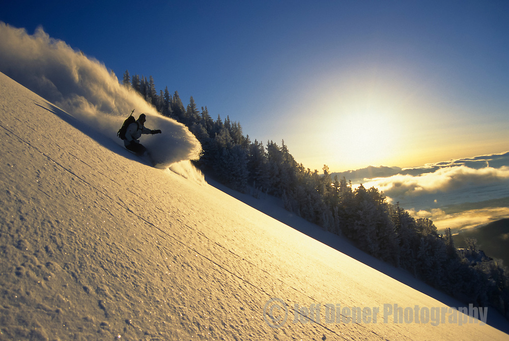 A snowboarder carves a turn in fresh powder on Teton Pass, Jackson Hole, Wyoming.