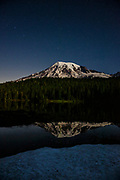 Stars fill the twilight sky over Mount Rainier, which is reflected in one of the Reflection Lakes in Mount Rainier National Park, Washington. The seven stars that make up the Big Dipper are visible just to the left of the volcano's summit. Mount Rainier, which has a summit of 14,411 feet (4,392 meters), is the highest mountain in Washington state and largest volcano in the Cascade Range.