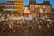 Sitting on the steps along the Ganges River, Hindu men perform a bathing ritual together. For Hindu's a bath in the Ganges is meant to cleanse the soul more than the skin.