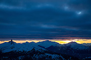 Moody photo of Black Tusk and Tantalus Range at sunset with low lying cloud cover over the coast mountains in Whistler, British Columbia as seen from 7th Heaven on Blackcomb Ski Area