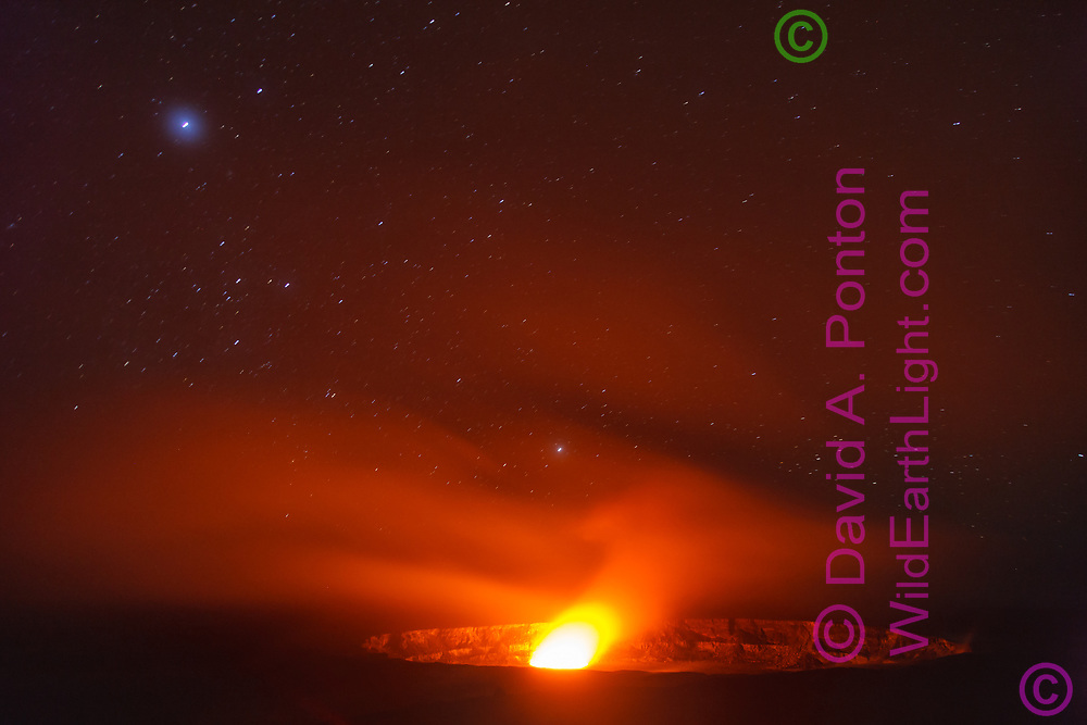 Occasional lava pool excursion inside the Halema'uma'u vent lights up the Kilauea crater and smoke from the vent, here under the stars of the night sky, Hawaii, © 2010 David A. Ponton