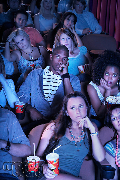 People sitting leaning on arms Watching Boring Movie