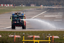 © Licensed to London News Pictures. 29/02/2016. Gatwick, UK. An airport fire engine spraying liquid over an area of spillage as tractors with cleaning equipment wait to clean the runway at Gatwick Airport in West Sussex, where the main runway has been closed due to a spillage. Photo credit: Peter Macdiarmid/LNP
