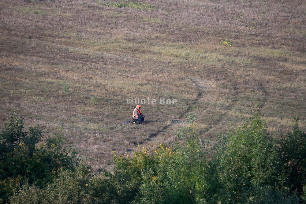 hunter sitting in a field waiting for the animals to arrive