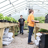 Lauren Wood | Buy at photos.djournal.com<br /> Students Dylan Boydstun, left, and Brody Hall prune plants before customers arrive in the greenhouse Wednesday at Pontotoc Middle School.