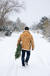 cowboy walking with a Christmas Wreath on a snowy road