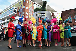 © Licensed to London News Pictures. 09/04/2016. Liverpool, UK. A group of brightly dressed ladies pose for a picture on Grand National day of the Grand National 2016 at Aintree Racecourse near Liverpool. The race, which was first run in 1839, is the most valuable jump race in Europe. Photo credit : Ian Hinchliffe/LNP