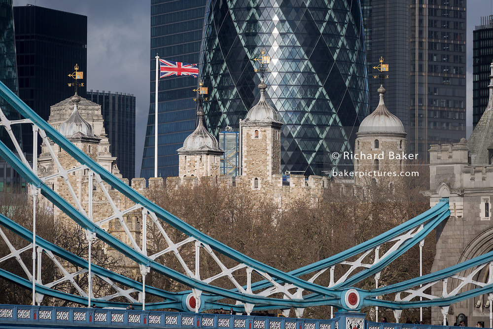 Weeks before the UK's Brexit from the European Union (31st January 2020), the British Union Jack flag flies over the Norman-era Tower of London and the northern steel suspension chains and hangers of Tower Bridge, on 17th January 2020, in London, England.