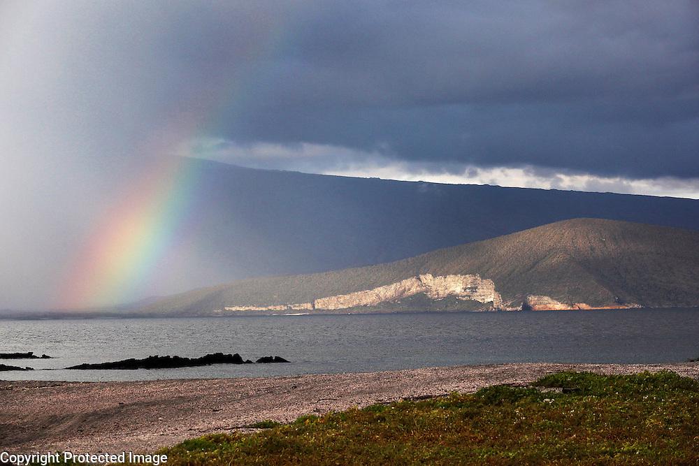 A rainbow arcs over Fernandina Island in the Galapagos.