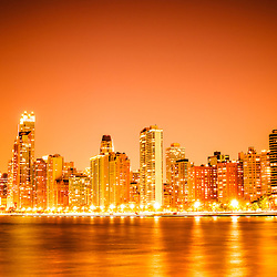 Photo of Chicago skyline at night with an orange sky. Includes the famous John Hancock Center skyscraper one of the tallest buildings in the world. Photo is large high resolution and was taken in 2012.