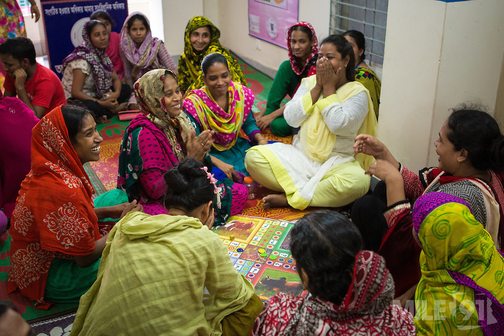Garment workers playing a board game during a cafe meeting organised and hosted by Awaj Foundation, Dhaka, Bangladesh.<br /> <br /> Awaj Foundation was founded by Nazma Akter in 2003 to support and empower garment workers to negotiate safer and fairer working conditions in factories.