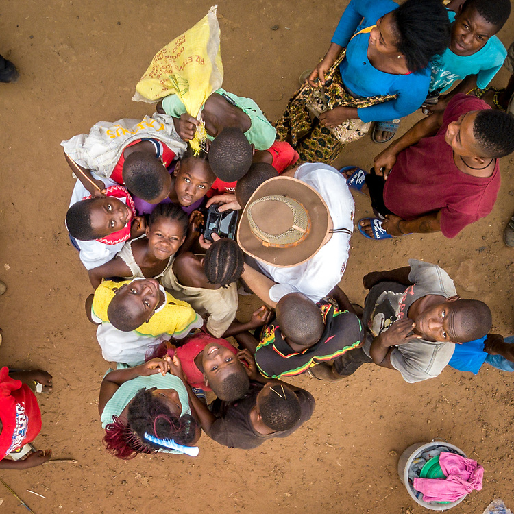 Aerial image of kids crowding around a drone photographer in Ganta, Liberia