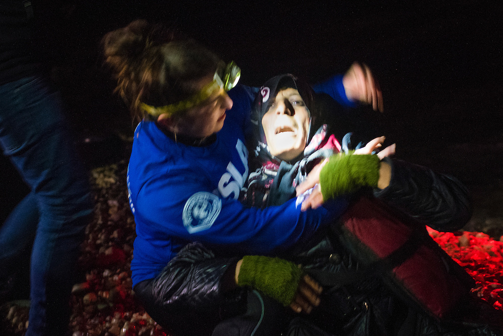 Amina Ramadan is cared for by a volunteer lifeguard as rescue workers attempt unsuccessfully to resuscitate her husband Mohamed moments after arriving on Lesbos Island on March 20, 2016 near Mitilini, Greece. Her boat contained approximately 71 people, including another man who also died on the journey.