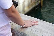 woman hand resting on marble bridge railing in Venice Italy