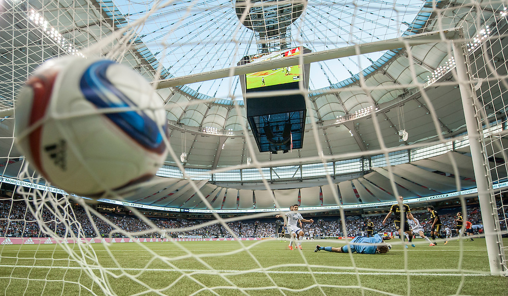 MLS Soccer- Vancouver Whitecaps FC vs. the Columbus Crew SC at BC Place Stadium in Vancouver:  Whitecaps Nicolas Mezquida celebrates as Columbus Crew goalkeeper Steve Clark  lies on the ground after a Vancouver goal..