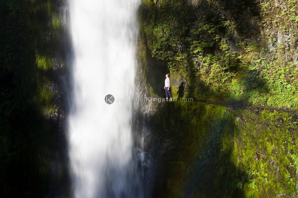 A young woman, looks in wonder at the beautiful Tunnel Falls on Eagle Creek trail in the Columbia River Gorge, Oregon, USA. Tunnel Falls received its name due to a tunnel being cut from the bedrock behind the falls so that hikers and trail runners can pass further up the gorge.  The trail becomes very narrow during this section and it is necessary to hold onto a safety cable. (Model Released)