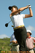 Fifteen year old Michelle Wie tees off while professionals from the PGA tour look on during a practice round prior to The 2005 Sony Open In Hawaii. The event was held at the Waialae Country Club in Honolulu, Hawaii.