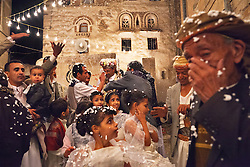 Relatives and neighbors celebrate bridegroom Ameen Ararah, in floral head scarf, at center rear, 21, at his wedding in Sana's Old City, Yemen, April 1, 2012. In a country where nearly half the population lives on $1.45 a day, wedding expenses, which can exceed $5,000, are prohibitive. Many couples now pool resources and marry in groups.