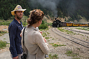 Tourists watch as the Durango Silverton Railroad make a scheduled stop in downtown Silverton, engineers make preparations for the return trip south in Cascade Canyon and on to Durango, Colorado.