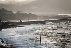 © Licensed to London News Pictures. 25/11/2017. Aberystwyth, Wales, UK. Waves crashing into the promenade on a bitterly cold and breezy day, with heavy rain showers  and hailstorms, in Aberystwyth. Photo credit: Keith Morris/LNP