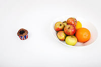 Fresh fruits in plate with cupcake against white background