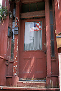 Old red door with an American flag in window