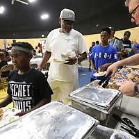 """Akeyo McGaha, 11, of Baldwyn, walks through the dinner line with his Grandfather Willie Wilson, as they attend the """"Father Son Fun Day"""" at Theron Nichols Park Thursday night in Tueplo. The Family Resource Center, Tupelo Police Athletic League and Real Men Stand Up, partnered to host the event."""