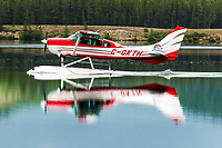 Alpine Aviation's latest Cessna 206 glides by for a southbound departure on a calm Schwatka Lake morning.