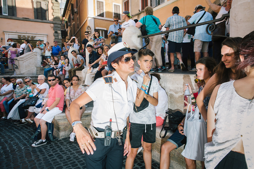 ROME, ITALY - 20 JUNE 2017: A Roman policewoman, entrusted to protect the Fountain of Trevi, warns students that are behaving badly by the fountain in Rome, Italy, on June 20th 2017.<br /> <br /> The warm weather has brought a menacing whiff of tourists behaving badly in Rome. On April 12, a man went skinny-dipping in the Trevi fountain resulting in a viral web video and a 500 euro fine.<br /> <br /> Virginia Raggi, the mayor of Rome and a national figurehead of the anti-establishment Five Star Movement,  issued an ordinance involving harsher fines for eating, drinking or sitting on the fountains, for washing animals or clothes in the fountain water or for throwing anything other than coins into the water of the Trevi Fountain, Bernini&rsquo;s Four Fountains and 35 other city fountains of artistic or historic significance around the city.  &ldquo;It is unacceptable that someone use them to go swimming or clean themselves, it&rsquo;s an historic patrimony that we must safeguard,&rdquo; Ms. Raggi said.