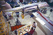 "Workers and aviation mechanics assemble a corporate jet aircraft. -MODEL RELEASED- Determine pricing and license this image, simply by clicking ""Add To Cart"" below --"