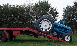 © Licensed to London News Pictures. <br /> 20/09/2014. <br /> <br /> Stokesley, England<br /> <br /> A man drives his vintage tractor from a lorry at the start of the Stokesley Agricultural Show in North Yorkshire, England. The show which dates back to 1859 is the largest one day agricultural show in the north of England.<br /> <br /> Photo credit : Ian Forsyth/LNP