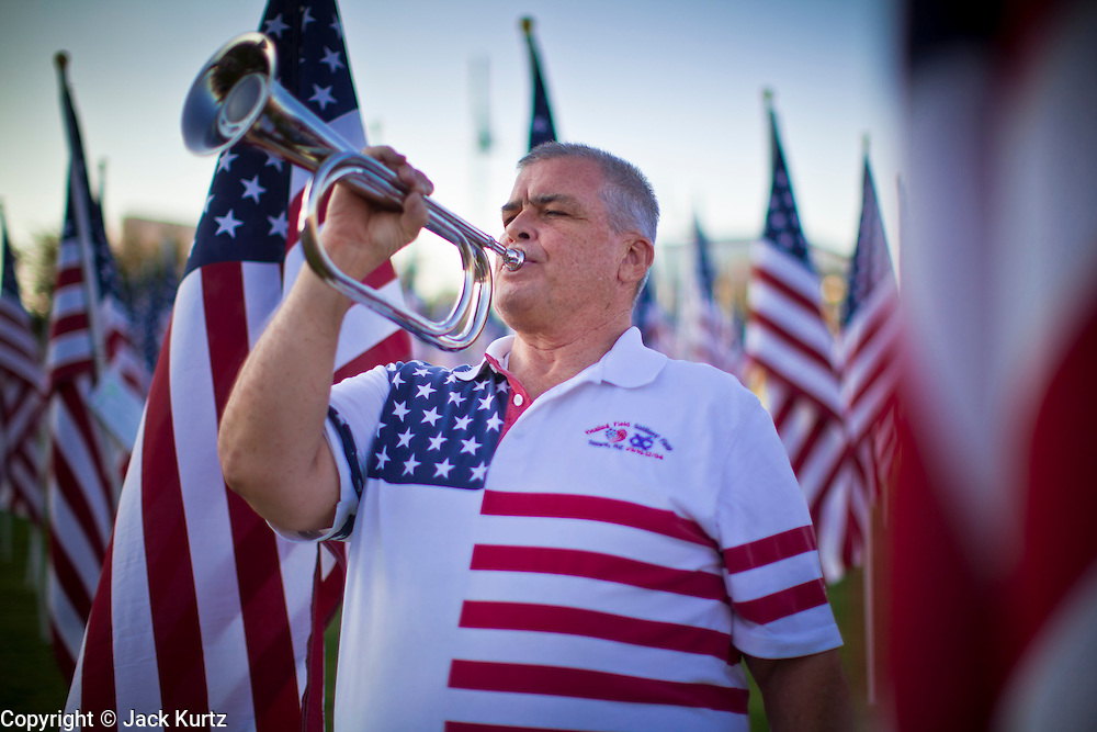 """10 SEPTEMBER 2011 - TEMPE, AZ:     MICHAEL WHITAKER, from Chandler, AZ, plays Taps in the """"Healing Field"""" in Tempe Saturday. The """"Healing Field,"""" a display of 2,996 flags, one for each person killed in the September 11 terrorists attacks on the World Trade Center in New York City and Washington DC, have become an annual tradition in Tempe, AZ. The event is sponsored by the National Exchange Club.     PHOTO BY JACK KURTZ"""
