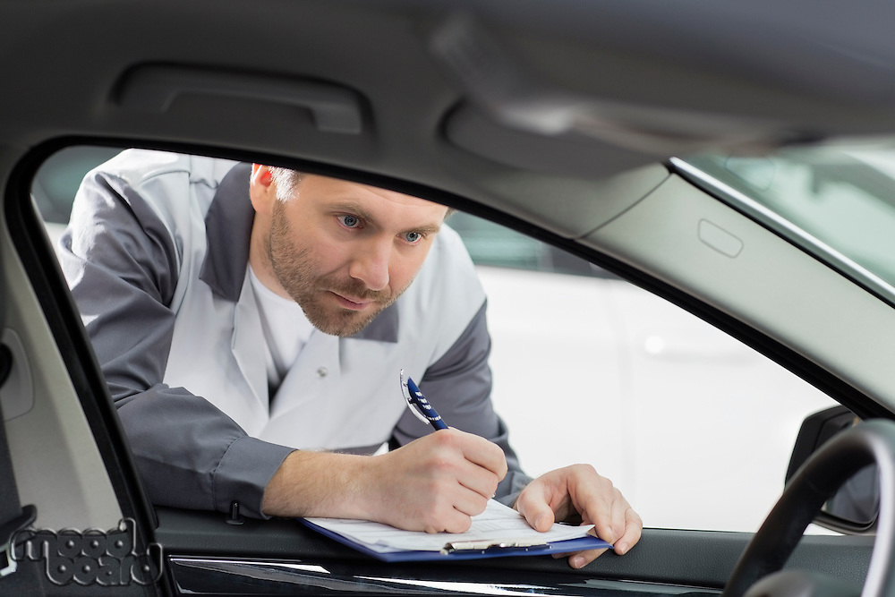 Male mechanic with clipboard checking car's interior in repair shop