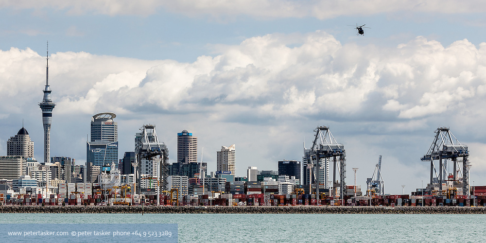Helicopter descending over the Auckland container terminal before landing at Mechanics Bay Heliport.  Downtown Auckland and the Skytower form part of this horizontally separated cityscape