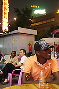 23 October 2007 - Guangzhou, China - Faith Atohoun (foreground), 24, from Togo sits in an outside entertainment venue preferred by Africans. He wants to be a fashion designer and has come to Guangzhou to try to realise his dream. By some estimates over 10,000 Africans from many different nations live and pass through Guangzhou which has overtaken Hong Kong as the new hub for African businessmen looking to cut out the middle man. Some come for a few weeks, others years. These African traders, most of whom come from West African nations like Ghana, Togo and Nigeria, profit by purchasing cheap goods direct from Chinese factories and then sending them back to their home countries where they can be sold at higher prices. Photo Credit: Luke Duggleby
