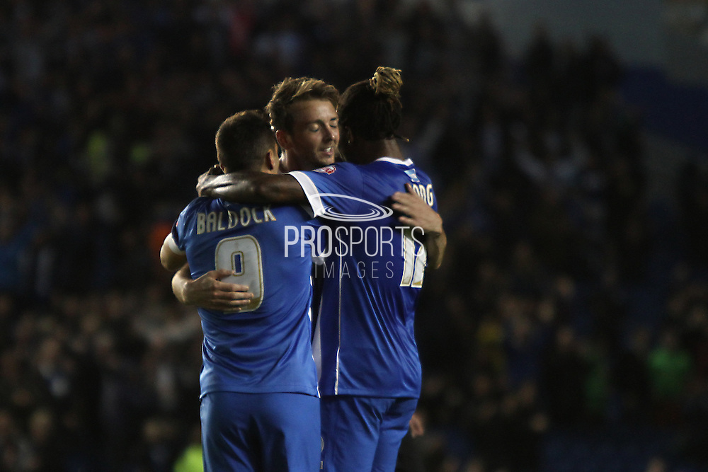 Brighton central midfielder, Dale Stephens celebrates with team mates Sam Baldock and Gaetan Bong after scoring Brightons second goal during the Sky Bet Championship match between Brighton and Hove Albion and Rotherham United at the American Express Community Stadium, Brighton and Hove, England on 15 September 2015. Photo by Geoff Penn.