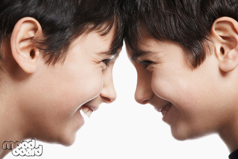 Twin boys (13-15) head to head laughing close-up