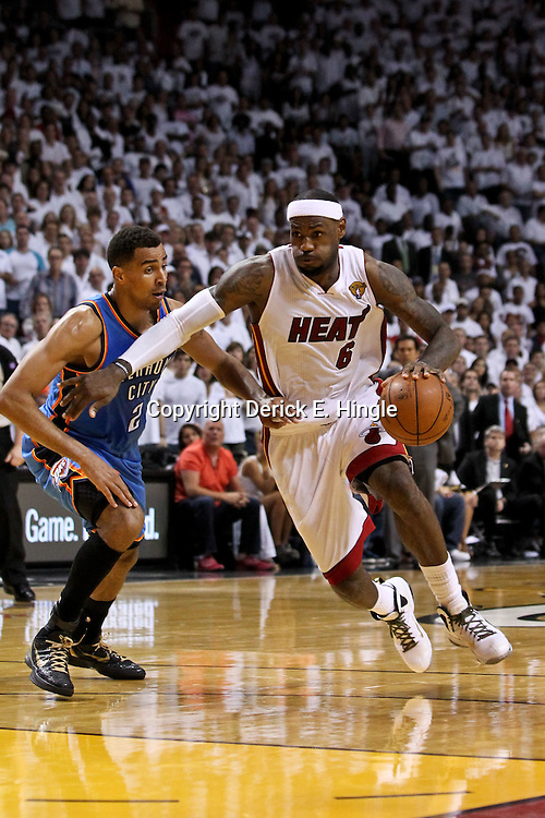 Jun 17, 2012; Miam, FL, USA; Miami Heat small forward LeBron James (6) drives past Oklahoma City Thunder shooting guard Thabo Sefolosha (2) during the third quarter in game three in the 2012 NBA Finals at the American Airlines Arena. Mandatory Credit: Derick E. Hingle-US PRESSWIRE