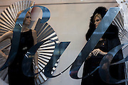 Fashion mannequins appear to be watching each other in womens' clothes shop window Sale sign.