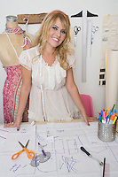 Portrait of female fashion designer working at desk