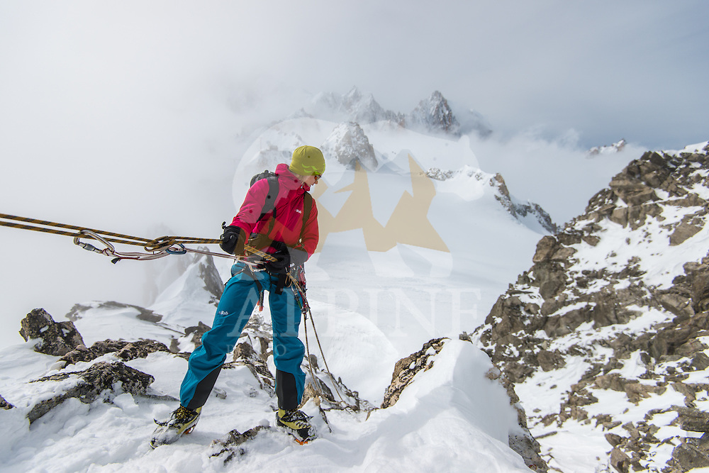 A female mountaineer as seen moments before the rappel of the ridge of Aiguille Marbrees on a cold and cloudy winter afternoon.