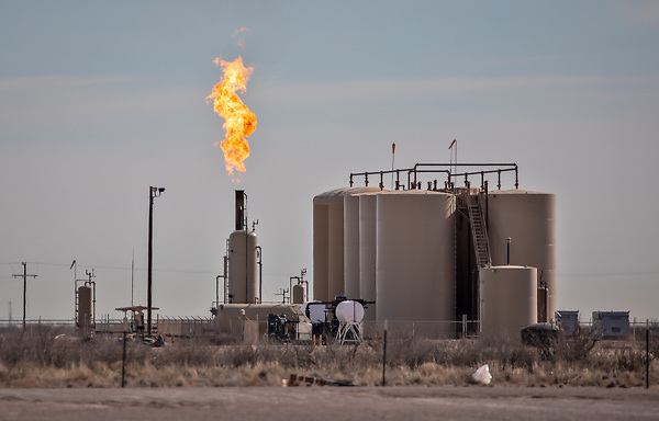 Flare at and oil and gas industry site on the outskirts of Midland Texas in the Permain Basin.